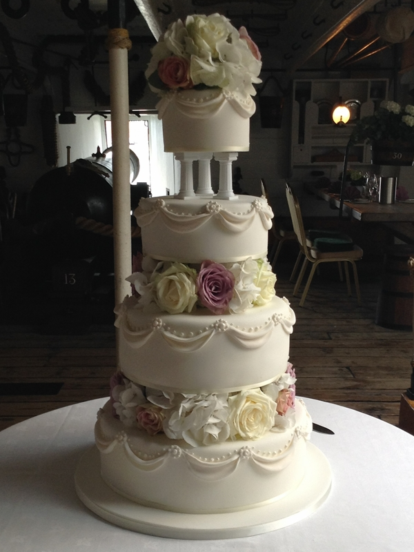 Fairytale wedding cake with fresh flowers pillars and swags