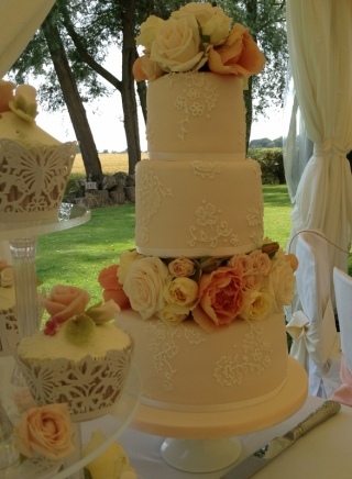 BESPOKE PEACH AND LACE WEDDING CAKE WITH FRESH FLOWERS. LACE CUPCAKES WITH SUGAR FLOWERS.